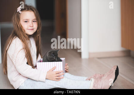 Smiling kid girl 4-5 year old sitting on floor holding box with kitten closeup. Birthday surprise. Friendship. Childhood. - Stock Photo