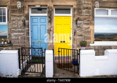 Colourful Wooden Front Doors of two traditional British Terraced Houses. One Door is Light Blue while the other is Bright Yellow. - Stock Photo