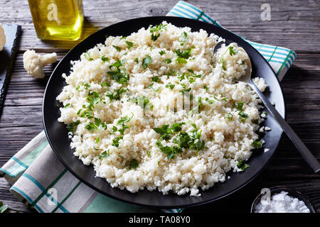 close-up of Cauliflower rice or couscous mixed with finely chopped parsley in a black bowl on an old rustic table,  horizontal view from above - Stock Photo