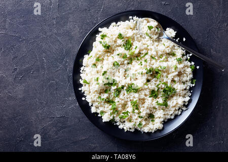 close-up of Cauliflower rice or couscous mixed with finely chopped parsley in a black bowl on a concrete table, horizontal view from above, flatlay - Stock Photo