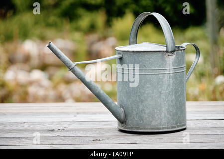 Old metal watering can standing on  wooden floor of a terrace in front of a beautiful springtime garden - Stock Photo