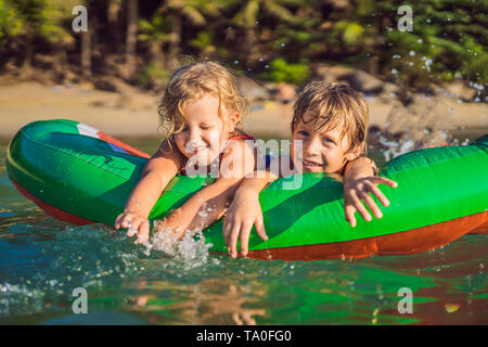 Children swim in the sea on an inflatable mattress and have fun - Stock Photo