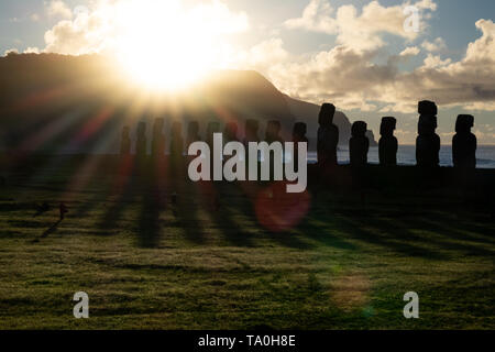 Bright sun rising behind Moais in Easter Island - Stock Photo