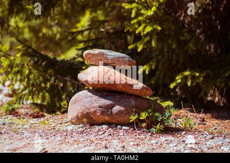 Stones pyramid on pebble beach symbolizing stability, zen, harmony, balance.Stone Pyramids. - Stock Photo