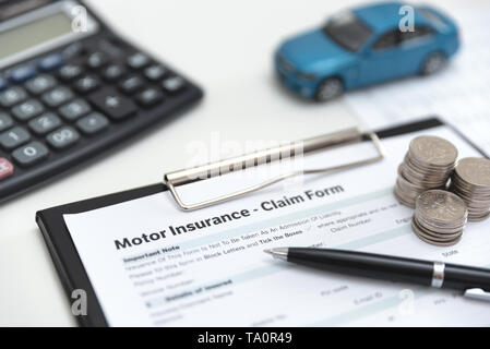Motor or car insurance claim form with coin stack, calculator and car model. - Stock Photo