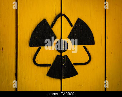 Sign of radiation on a yellow wooden board. - Stock Photo
