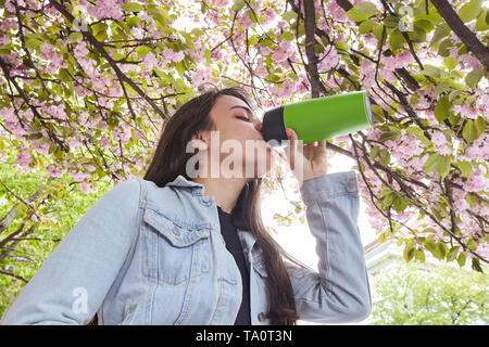 Young girl drinking and enjoying in sunshine standing outdoor in sun light on the background of blooming sakura - Stock Photo