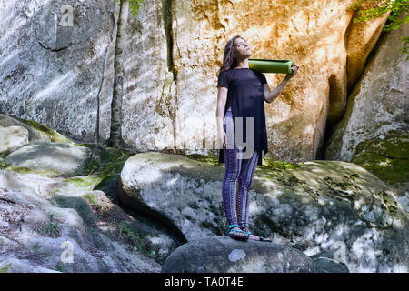 Young attractive girl stand on the big rock in forest and holding a yoga mat and a cup. Preparing for practicing yoga on a yoga mat. - Stock Photo