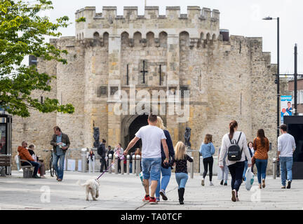 People shopping in Southampton Above Bar ( high street)  with the Bargate in the background - Stock Photo