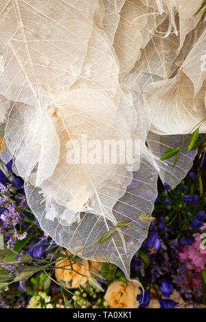 Beautiful, delicate arrangement of flowers and leaves including the dead skeleton of leaf veins - Stock Photo