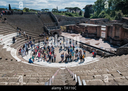 Tourists in the theatre excavated from the ruins of Pompeii  the ancient Roman city near Naples in the Campania region of Italy - Stock Photo