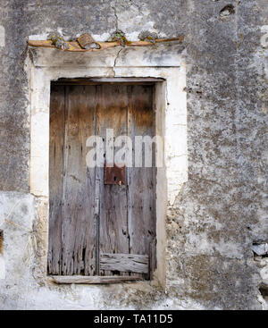 Ancient worn out dilapidated weathered faded wooden door with rusty lock - Stock Photo