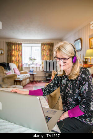 A mother working at home,online with her computer smiling at her monitor screen with amusement. - Stock Photo
