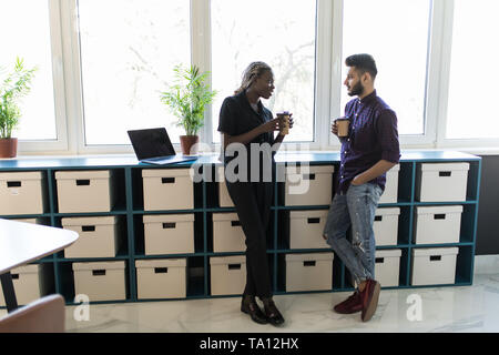 Business colleague having coffee break in the office - Stock Photo