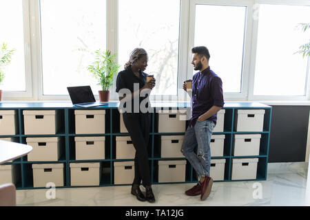Two business coworkers communicated in comfortable office during coffee break. Handsome indian guy talking with african woman holding hot drinks.