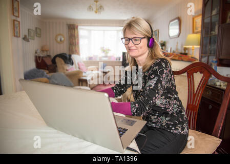 A mother working at home,online with her computer looking at her monitor screen with interest. - Stock Photo