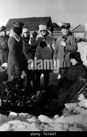 German officers and soldiers of the Wehrmacht are holding a briefing at a machine-gun post in the surrounded Demyansk. Photo of the Propaganda Company (PK): war correspondent Beissel. - Stock Photo