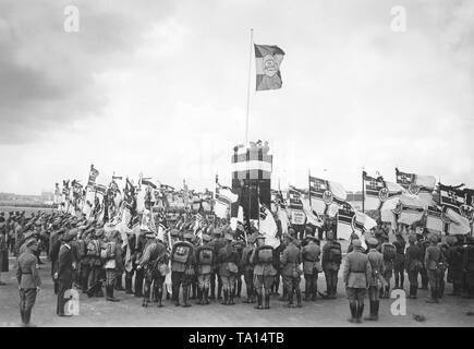 As part of the 13th Reichsfrontsoldatstag (Frontline Soldiers' Day), the 2nd leader of the Stahlhlem, Theodor Duesterberg, dedicates the Reichskriegsflaggen (imperial war flags) of 40 newly founded local groups. On a flagpole is a flag with the logo of the Stahlhelm. - Stock Photo