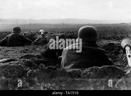 Soldiers of the Wehrmacht in their foxholes awaiting the onslaught of the Red Army in Berlin. Beside the soldiers there are anti-tank rocket launchers, often the only remaining weapon against the Russian tanks. - Stock Photo