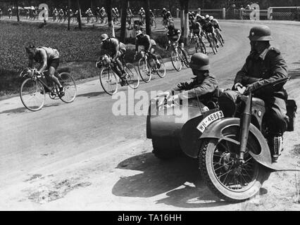 In the stage Chemnitz-Erfurt on June 8, 1937, the third stage of the tour of Germany, the main field of cyclists passes two motorcyclists of the Wehrmacht. - Stock Photo