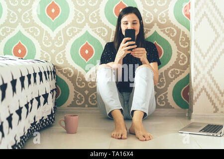 Brunette babe millenial is talking on the phone in social network and having fun time. Concept blogging and online community. - Stock Photo