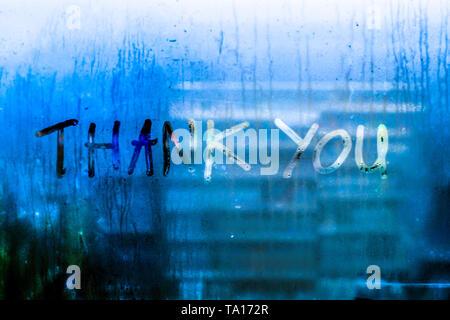 Thank you words rain drops water drops written wrie on window glass blue tone blur nature bokeh background - Stock Photo