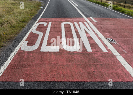 Slow warning sign written on the road in England. Slow road marking - Stock Photo