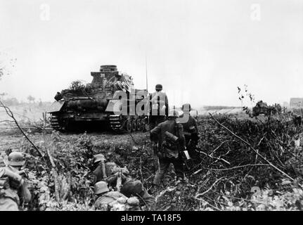 An Panzer IV and infantry of the Wehrmacht are slowly moving through a minefield. 6th Panzer Division, Division Army Group North near Leningrad. - Stock Photo
