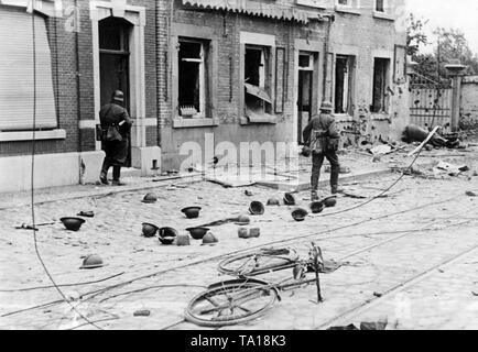 Two German infantrymen go through a French town. A dead horse and abandoned steel helmets testify the retreat of the French troops. - Stock Photo
