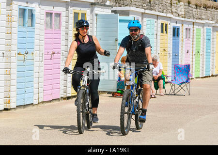 Lyme Regis, Dorset, UK.  21st May 2019. UK Weather.  Cyclists riding along the seafront at the seaside resort of Lyme Regis in Dorset enjoying a warm sunny day.   Picture Credit: Graham Hunt/Alamy Live News - Stock Photo