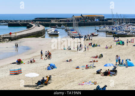 Lyme Regis, Dorset, UK.  21st May 2019. UK Weather.  Sunbathers on the beach at the seaside resort of Lyme Regis in Dorset enjoying a warm sunny day.   Picture Credit: Graham Hunt/Alamy Live News - Stock Photo