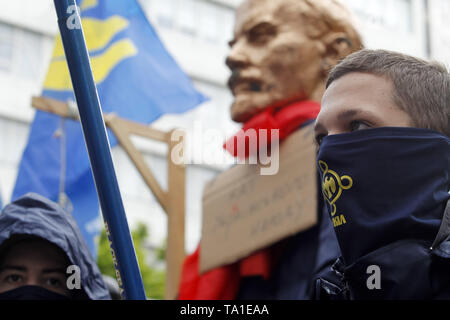 May 21, 2019 - Kiev, Ukraine - Activists wearing masks stand in front of a gallows and a sculpture of Soviet leader Vladimir Lenin placed of a fence of the Constitutional Court, during a protest against cancellation of the law on decommunization, in Kiev, Ukraine, on 21 May 2019. Activists protest against appeals of 46 lawmakers who appealed to the court for review the constitutionality of the law about decommunization. On May 21, 2015 the law on decommunization voted by the Ukrainian Parliament came into force, which prohibits the propaganda of the communist and national-socialist (Nazi) tota - Stock Photo
