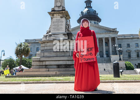Columbia, South Carolina USA - May 21, 2019: Activist R.M. wears a costume outfit that resembles that of the characters from the show 'The Handsmaid's Tale' while holding a sign that reads 'The Uterus is NOT State Property' during the South Carolina 'Stop The Ban' rally.  'Stop The Bans' rallies took place in all 50 U.S. states today serving as a direct resistance to the growing conservative attempt to overturn Roe Vs. Wade and remove a woman's right to have a legal and safe abortion. Credit: Crush Rush/Alamy Live News - Stock Photo