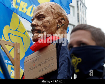 A gallows and a sculpture of the Soviet leader Vladimir Lenin with a placard  saying I am the executioner of the Ukrainian people is seen hanging on a fence of the Constitutional Court during the protest. Protesters stand against appeals of 46 Ukrainian lawmakers who appealed to the court to review the constitutionality of the law about decommunization. The law on decommunization was voted by the Ukrainian Parliament in April 2015, condemning communist and Nazi totalitarian regimes, banning their propaganda and symbolism. According to the law, the symbolic and propaganda of Nazism, National So - Stock Photo