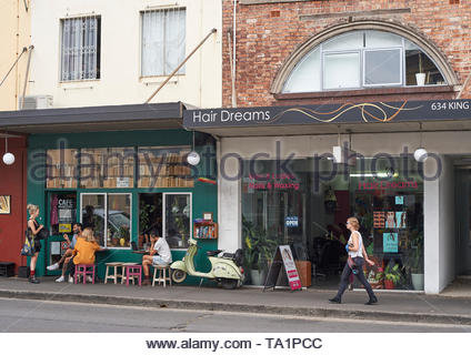 A female pedestrian walks past a hair-dressing salon, toward people outside a cafe / bookshop; in the inner Sydney suburb of Newtown, NSW, Australia. - Stock Photo