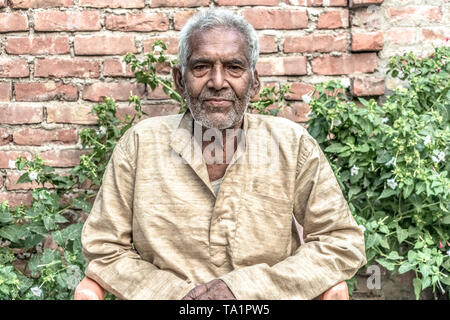 Portrait of Old aged Indian male in his 80s with white beard, wearing pale clothes, sitting relaxed in garden & leading satisfied post-retirement life - Stock Photo
