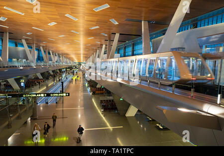 Elevated passenger shuttle train in terminal building at Hamad International Airport in Doha, Qatar - Stock Photo