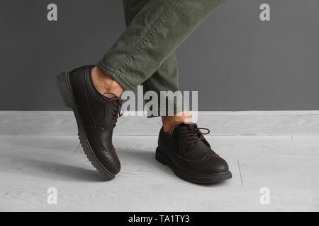 Legs of stylish handsome man standing near grey wall - Stock Photo