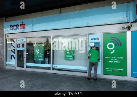 Man using an ATM / Bancomat, at a branch of the BCR bank, Banca Comercială Română, in the Old Town area of centeral Bucharest, Romania - Stock Photo