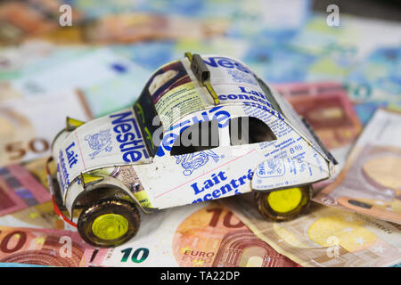 VIERSEN, GERMANY - MAY 20. 2019: Annual vehicle car cost concept - Model of car made of recycled cans on Euro paper money bank notes - Stock Photo