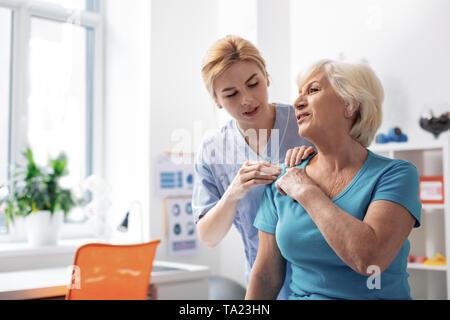 Nice professional female masseuse touching the shoulder - Stock Photo