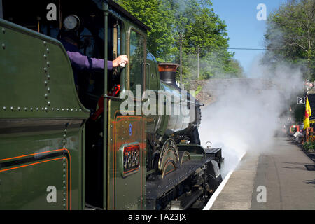 A steam locomotive leaving the platform of Bishops Lydeard railway station in Somerset, UK, with some steam blurring the more distant view. - Stock Photo