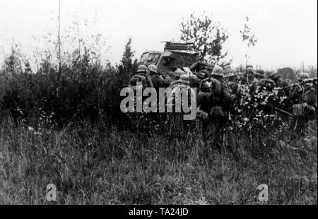 Several infantrymen are waiting in the cover of a battle tank (presumably Panzer III) for further orders. Photo of the Propaganda Company (PK): war correspondent Mauch. - Stock Photo
