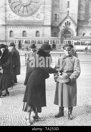 A uniformed Stahlhelm member with a matching helmet and collecting box collects donations from passers-by in front of the Kaiser Wilhelm Memorial Church on the corner of Tauentzienstrasse and Rankestrasse. - Stock Photo