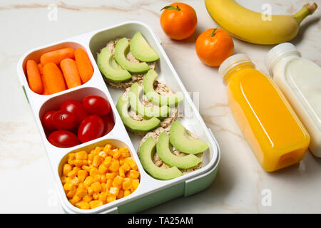 Lunch box with tasty food, fruits and bottles of drinks for kid on light table - Stock Photo