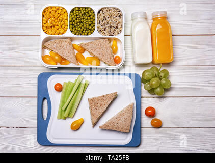 Lunch box with tasty food and bottles of drinks for kid on white table - Stock Photo