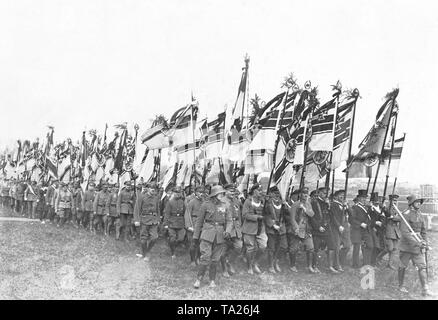 Delegations of the veteran associations march in field gray and steel helmets under the Reichskriegsflagge (imperial war flag), led by officers with drawn swords. - Stock Photo