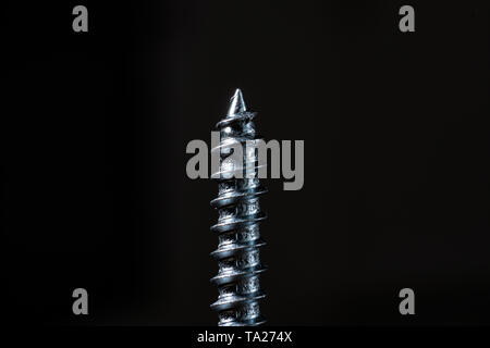 The one self-tapping screw on black background - Stock Photo