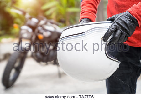 Handsome man holding a helmet and vintage motorcycle blur background, moto biker concept - Stock Photo