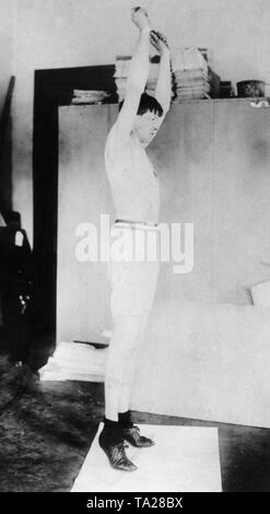 Ray Ewry during training exercises in his hotel room during the olympic games in London, 1908 - Stock Photo